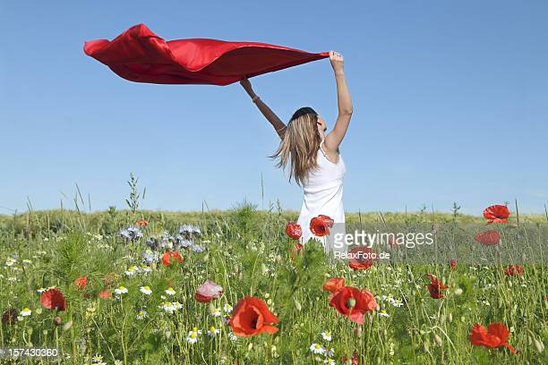 Woman Standing in Poppy Field Holding red scarf to Wind