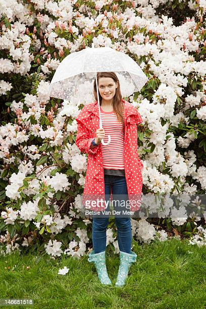 Woman standing in rain in front of rhododendrons.