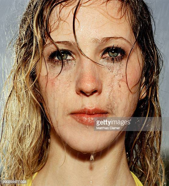 Woman standing in rain with smeared mascara, portrait, close-up