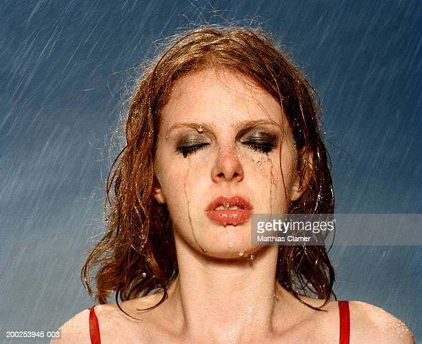 Woman standing in rain with smeared massacre, eyes closed, close-up