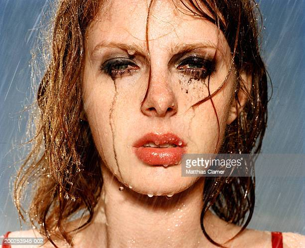 Woman standing in rain with smeared massacre, portrait, close-up