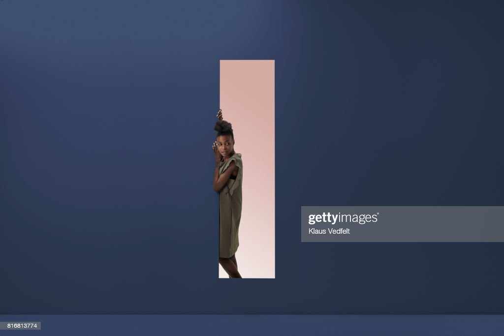 Woman standing in rectangular opening of coloured wall : Stock Photo