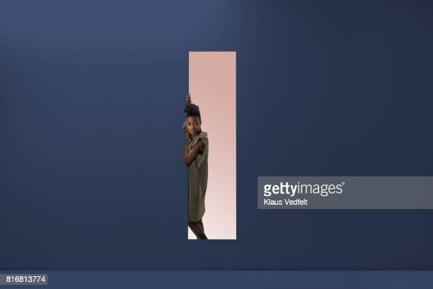 Woman standing in rectangular opening of coloured wall