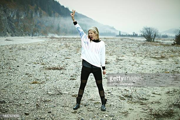 Woman standing in remote setting making peace sign