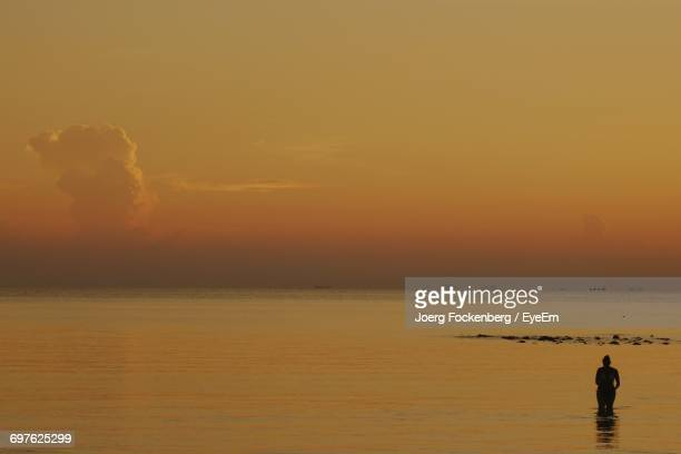 Woman Standing In Sea Against Orange Sky During Sunset