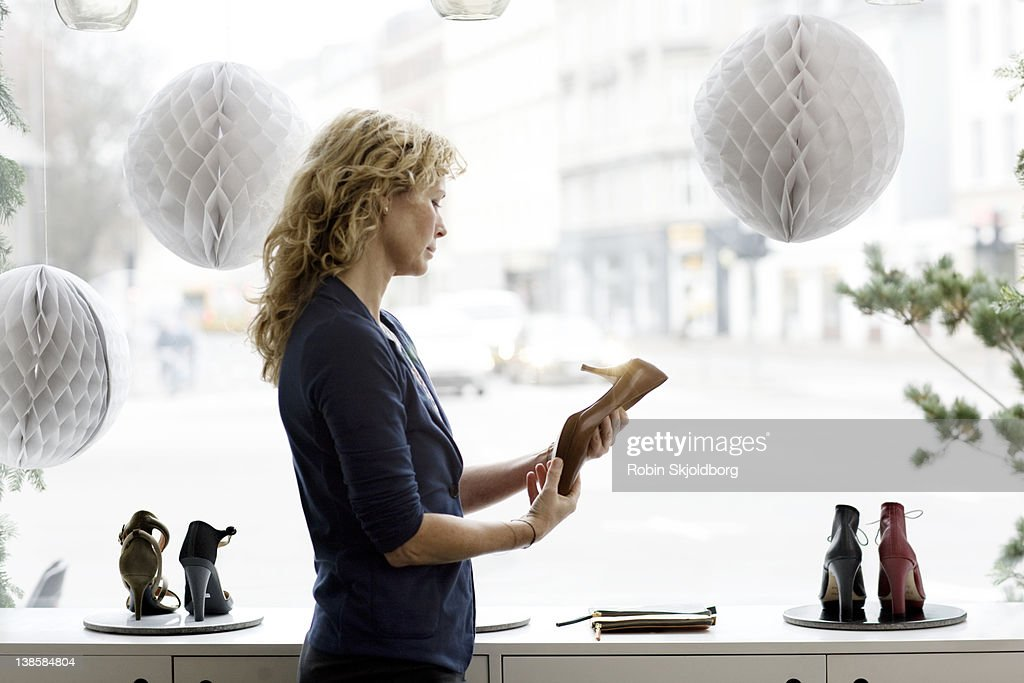 Woman standing in shoe store looking at shoes