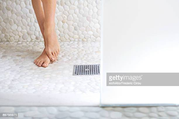 Woman standing in shower, cropped view of feet