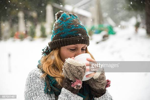 Woman standing in snow drinking a cup of tea