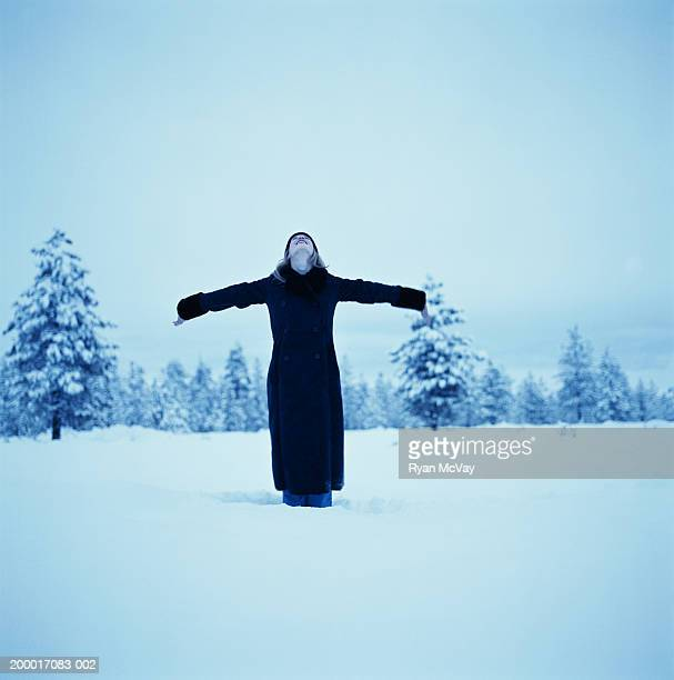 Woman standing in snow with head back and arms outstretched