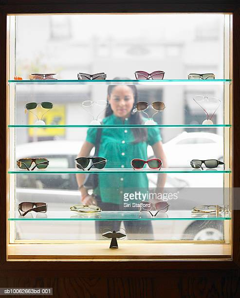 Woman standing in street, looking at window display of eyeglasses, view from inside shop
