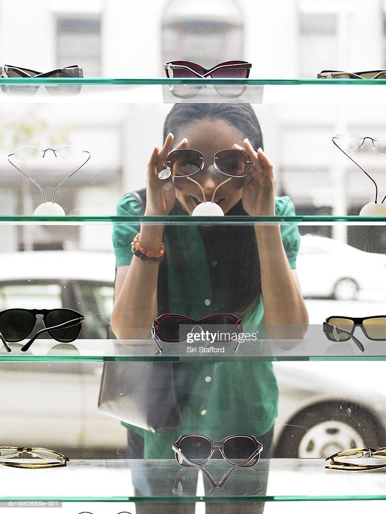 Woman standing in street, peering at window display of eyeglasses, view from inside shop