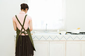 A woman standing in the kitchen, rear view