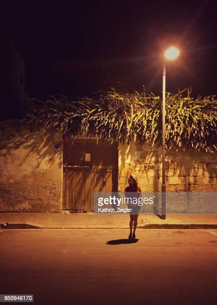 Woman standing in the light of a streetlamp, Sicily