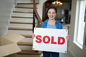 Woman standing in the living room holding sold sign at home