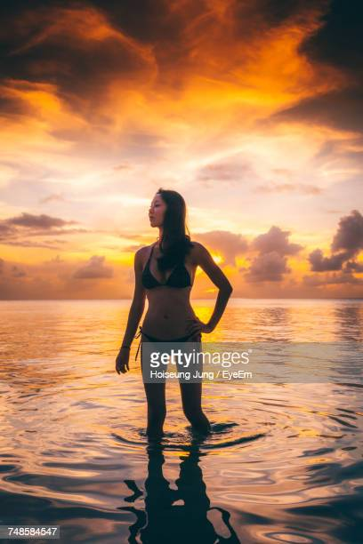 Woman Standing In Water At Beach Against Orange Sky During Sunset
