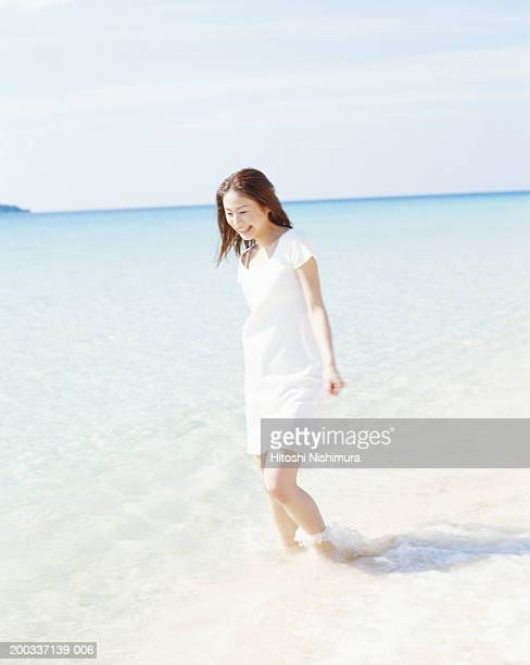 Woman standing in water on beach, smiling