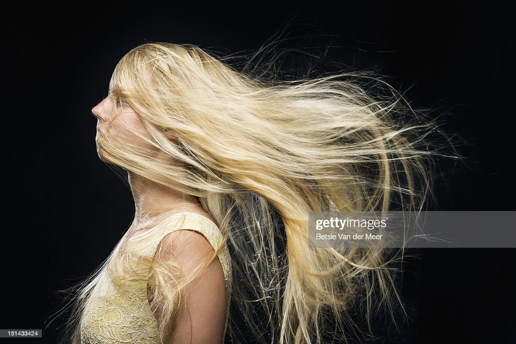 Woman standing in wind, hair covering face. : Stock Photo