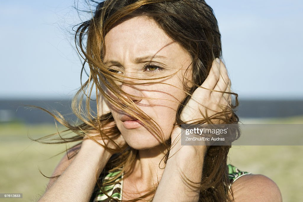 Woman standing in wind, hands holding hair down, close-up