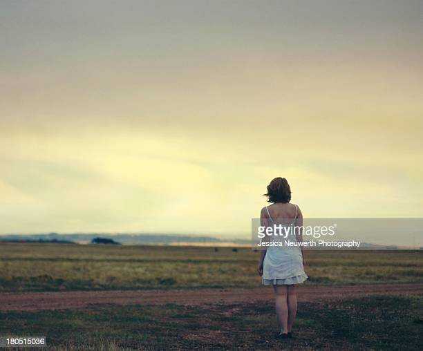 Woman standing in yellow field with back to camera