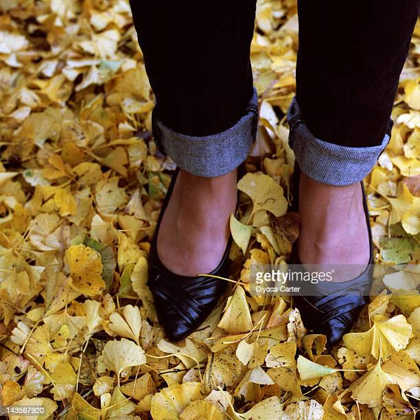 Woman standing in yellow ginkgo leaves