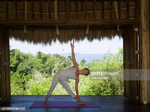 Woman standing in yoga position in hut