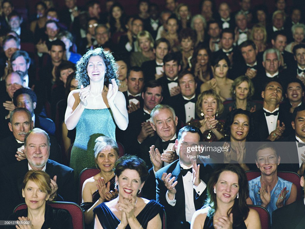 Woman standing it theater audience, applauding, portrait