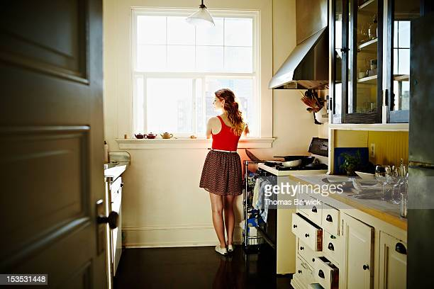 Woman standing looking out kitchen window