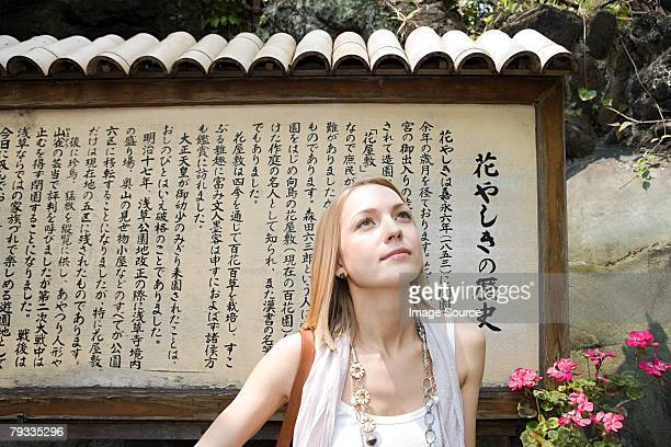 Woman standing near a japanese sign