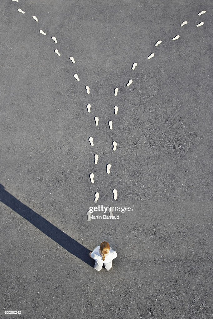 Woman standing near diverging line of footprints : Stock Photo