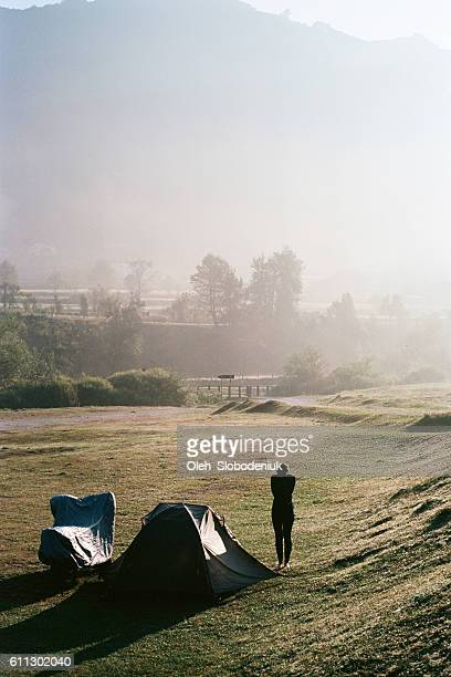 Woman standing near the tent and motorcycle