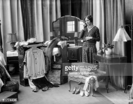 Woman standing near vanity table and dressing trunk filled with clothes. : Stock Photo