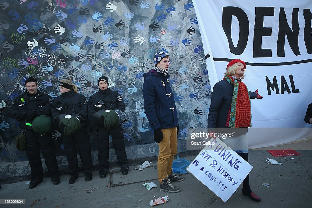 A woman standing next to a banner that reads: 'Monument' urges passers-by to sign a petition as police in riot gear stand guard at a section of the East Side Gallery, which is the longest still-standing portion of the former Berlin Wall, that is to be removed tomorrow by a construction company building a high-rise luxury apartment block on March 3, 2013 in Berlin, Germany. A real estate developer is planning to build a 14-storey apartment building between the East Side Gallery and the Spree River and needs to remove the Wall section in order to allow access to the construction site. Protesters managed to temporarily halt the dismantling of the section on March 1. Critics, including East Side Gallery mural artists and Spree River embankment development opponents, decry the move, citing the importance of the East Side Gallery's status as a protected landmark and a major tourist attraction. The East Side Gallery is approximately 1.3 kilometers long.