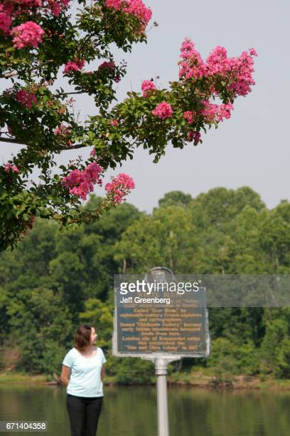A woman standing next to a historic marker next to Tombigbee River