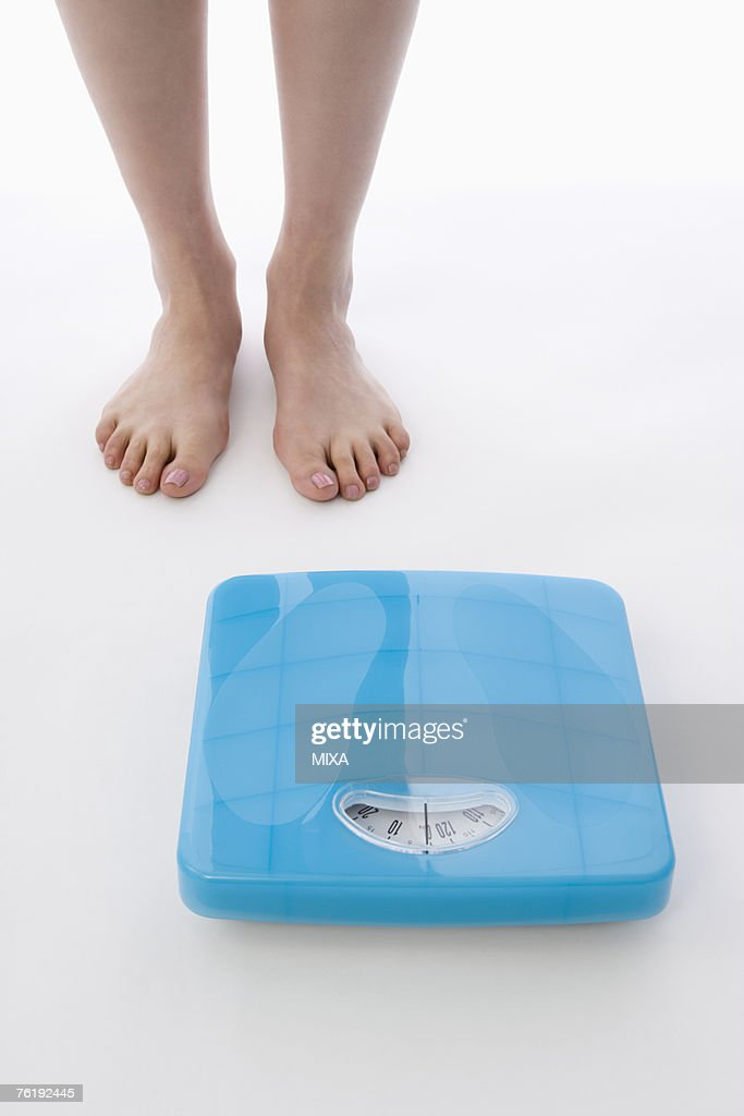 Woman Standing Next To Bathroom Scale Stock Photo