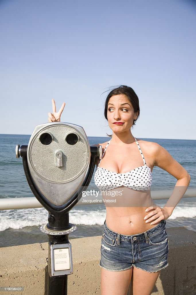Woman standing next to coin-operated binoculars