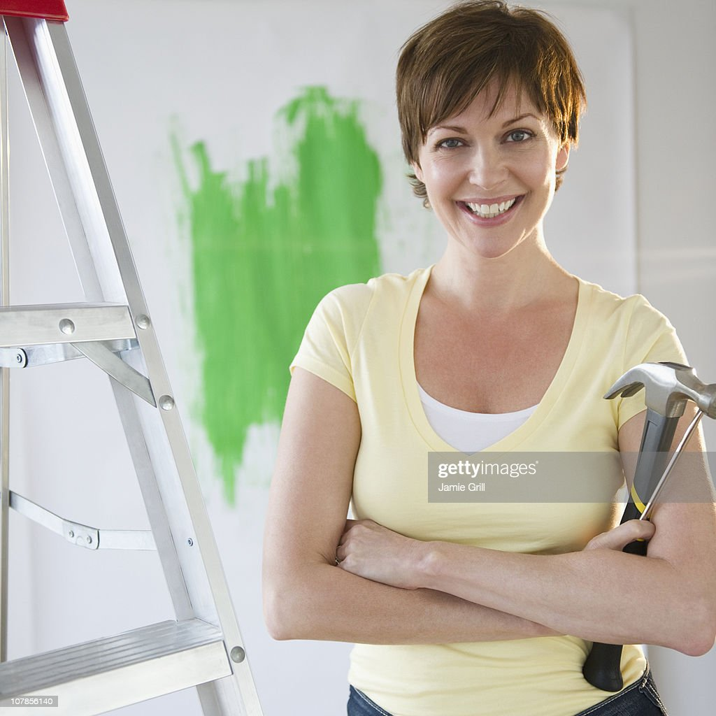 Woman standing next to ladder with tools : Stock Photo