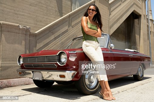 Woman standing next to vintage car