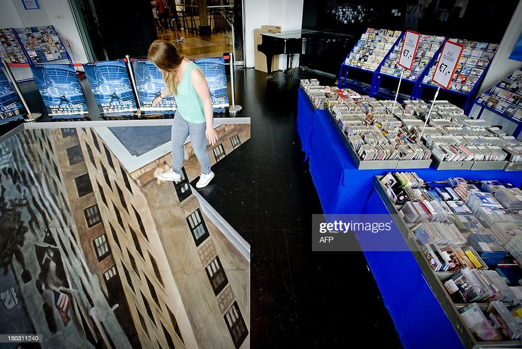 A woman standing on a 3D art picture in DVD shop 'Fame' in Amsterdam, on August15, 2012. The artwork was placed to mark the Dutch DVD release of the blockbuster movie 'Man on a Ledge'. AFP PHOTO/ANP ROBIN VAN LONKHUIJSEN netherlands out
