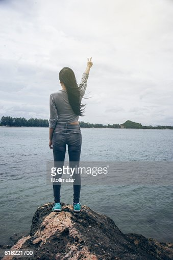 Woman standing on a cliff hill top,fighting or winner : Foto stock
