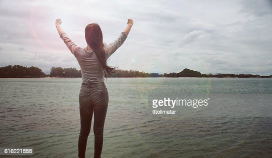 Woman standing on a cliff raising arms towards : Stock Photo