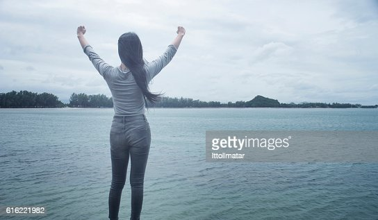 Woman standing on a cliff raising arms towards : Stock-Foto