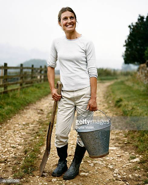 Woman Standing on a Country Lane Holding a Bucket and Spade