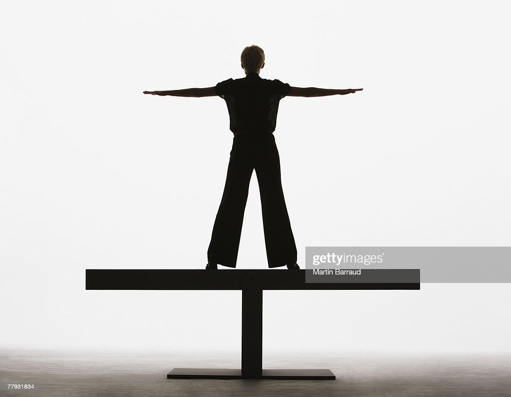 Woman standing on a plank with arms out : Stock Photo