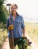 Woman Standing on a Rural Dirt Track Holding a Hoe and Vegetables