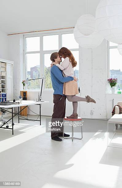 A woman standing on a stool with her arms around her boyfriend