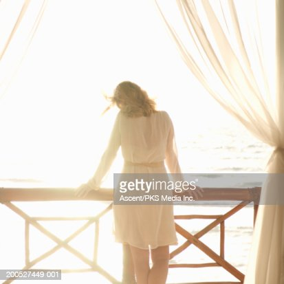Woman standing on balcony looking out to sea, rear view : Stock Photo