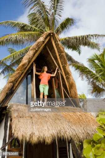 Woman standing on balcony of beach house : Stock-Foto