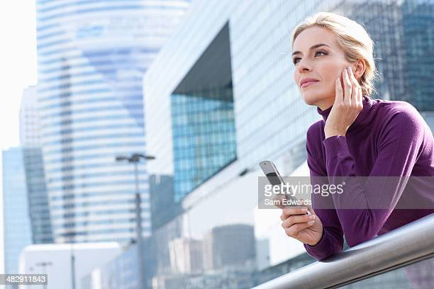 Woman standing on balcony with cellular phone