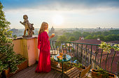 Female standing on romantic balcony with glass of fresh orange juice