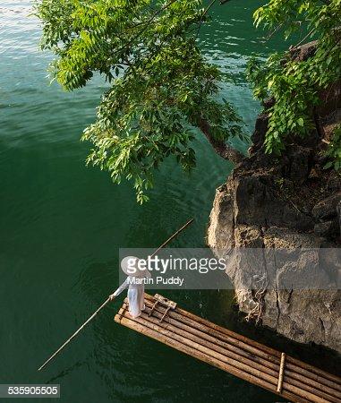 Woman standing on bamboo raft on lake